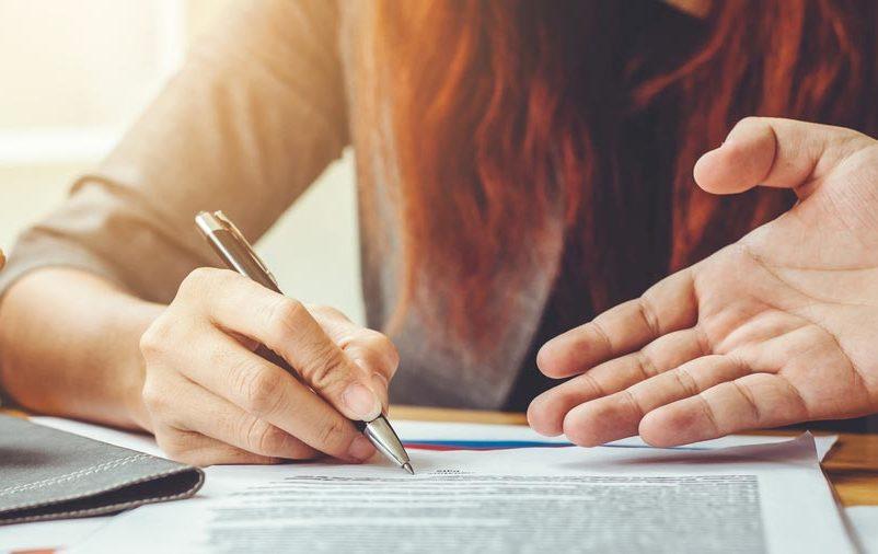 Mulher assina alguns documentos contábeis para entrega