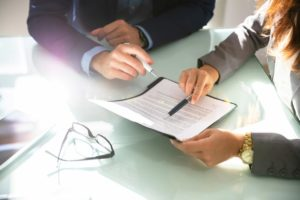 Dois profissionais em uma reunião com documentos contábeis