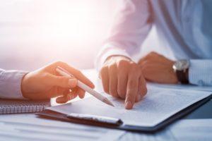 Profissional com caneta na mão examina os documentos contábeis