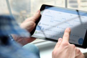 Dedos tocando em um tablet durante os serviços de despachante