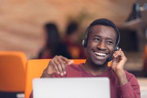 Homem sorridente realiza vendas por telemarketing