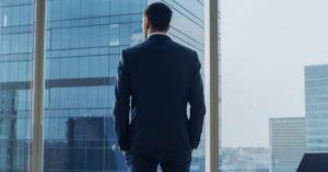 Executivo em frente a um prédio espelhado pensando em como reduzir o quadro pessoal de funcionários