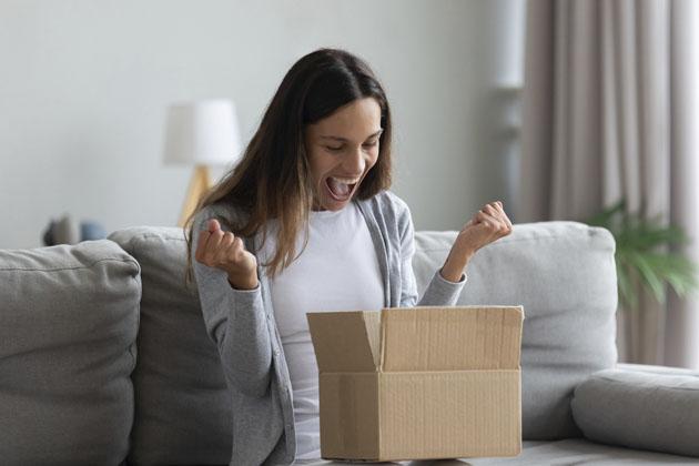 Mulher feliz ao receber suas entregas urgentes