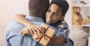 Pai e filho se abraçando durante a entrega de presentes do Dia dos Pais