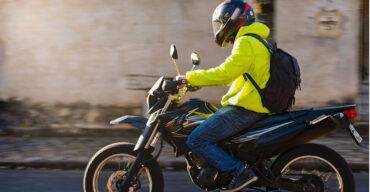 Motoboy com casaco verde sabe como pilotar moto no inverno