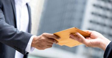 Dois profissionais realizando a troca de documentos na entrega de contrato